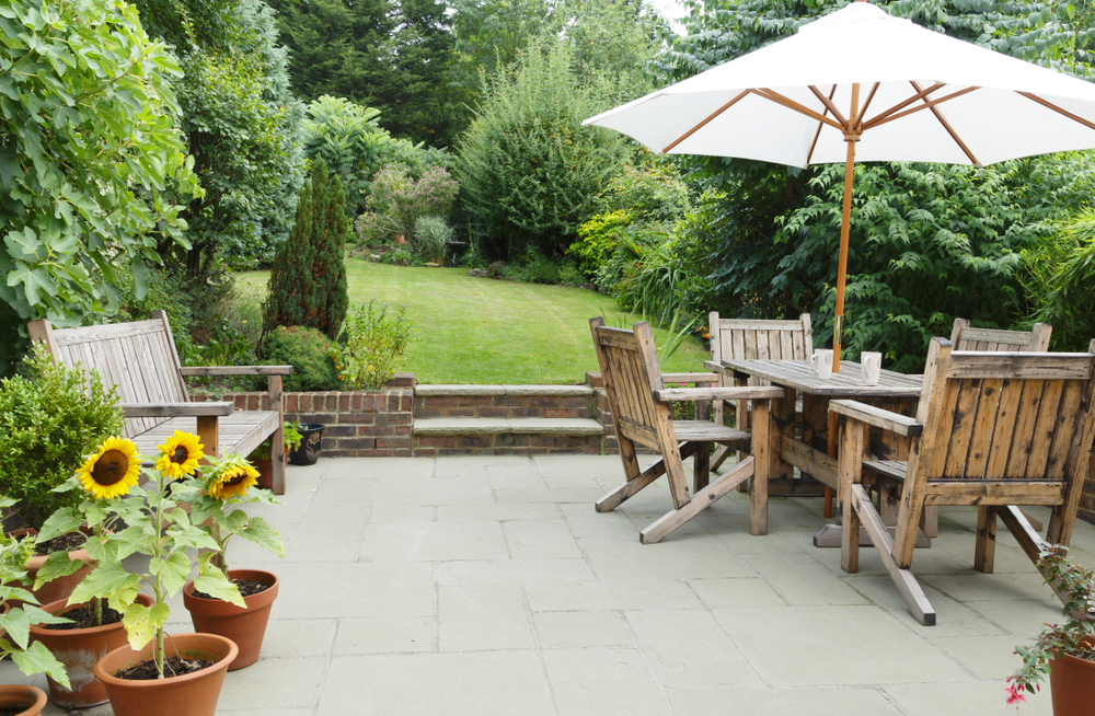 a simple patio with table and umbrella, french travertine