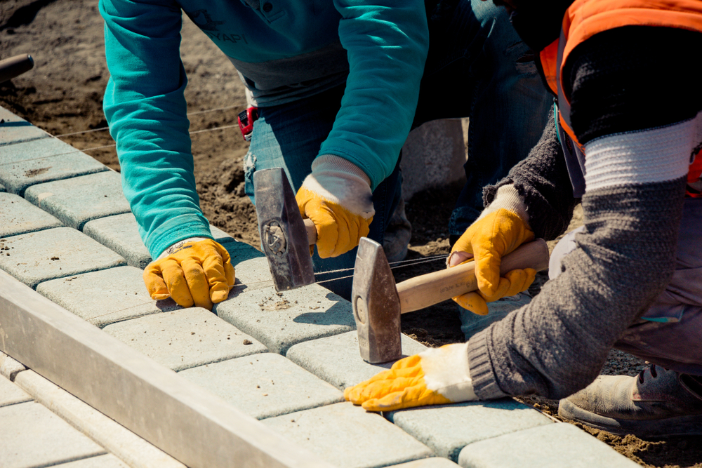 workers laying types of cobblestone pavers