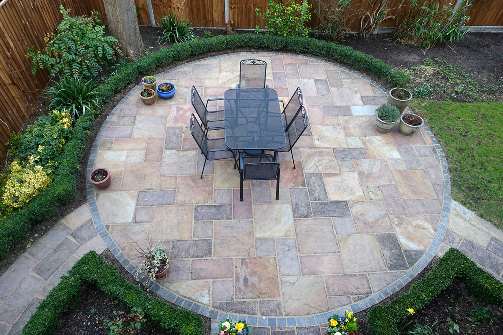 a backyard patio with varying paver sizes